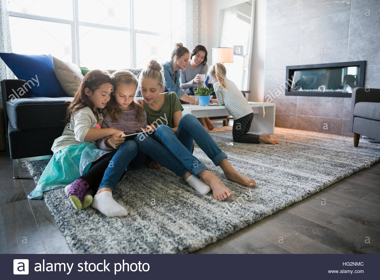Girls Enjoying Play Date Using Digital Tablet On Living Room Floor With Mothers In Background