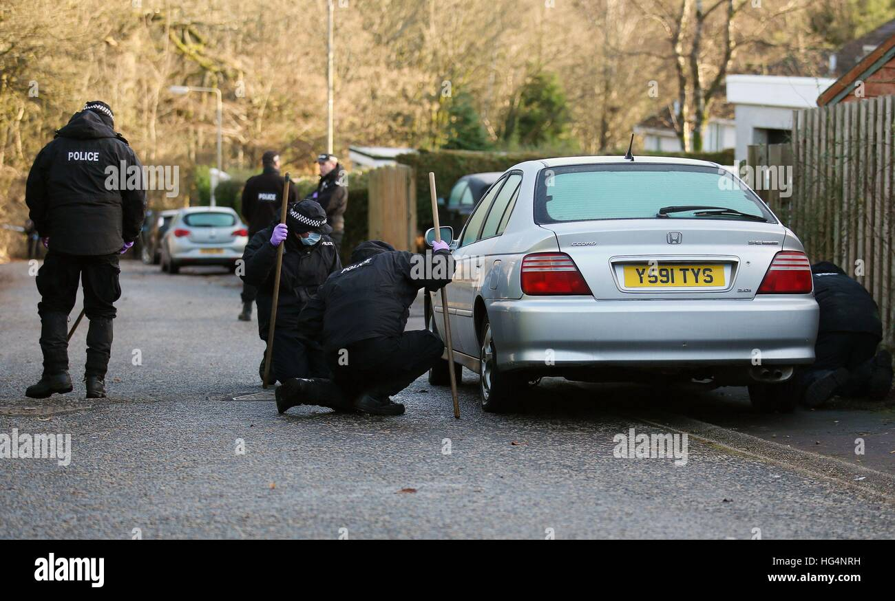 Police search a car near to the scene of a fire in Milngavie, East ...