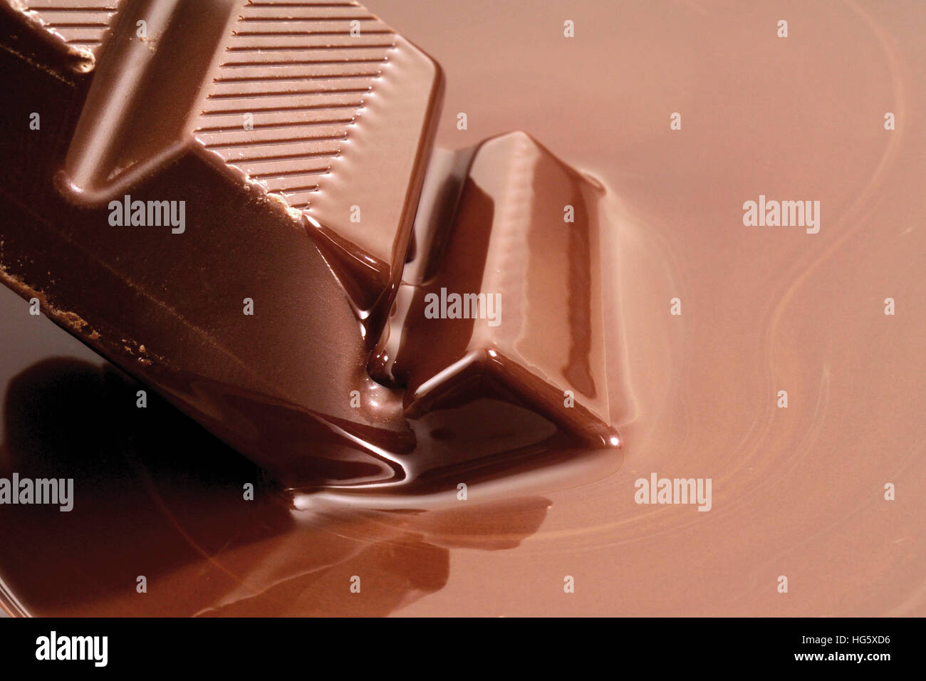 Chocolate bar dunked into melted couverture chocolate Stock Photo ...