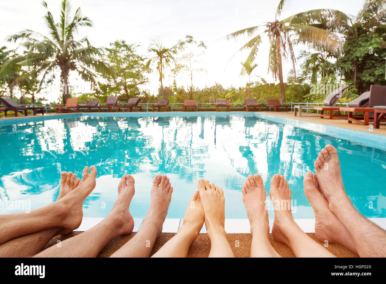 Family relaxing near swimming pool in hotel feet of group - Where is my nearest swimming pool ...