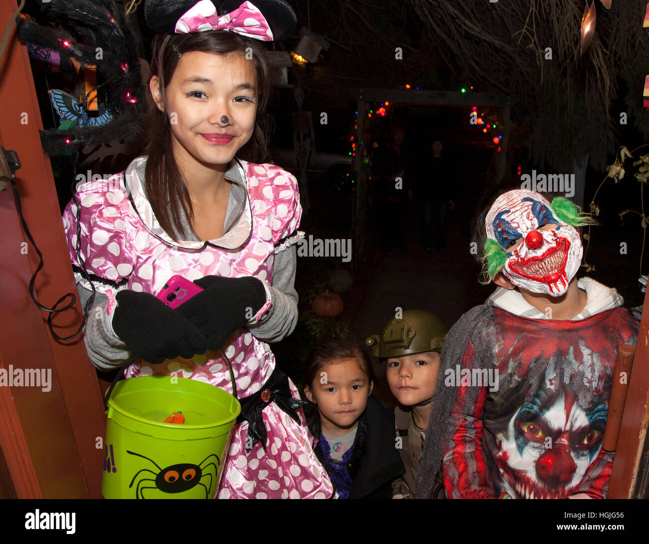 stock photo teen girl in polka dot dress and boy in a halloween evil scary clown costume trick or treating st paul minnesota mn usa