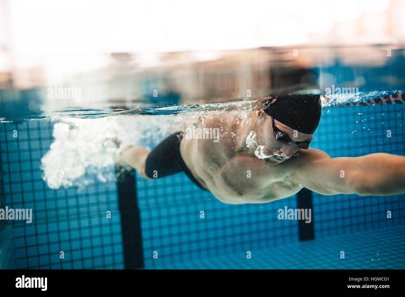 underwater shot of pro male swimmer in action inside swimming pool young sportsman training in the pool - Inside Swimming Pool