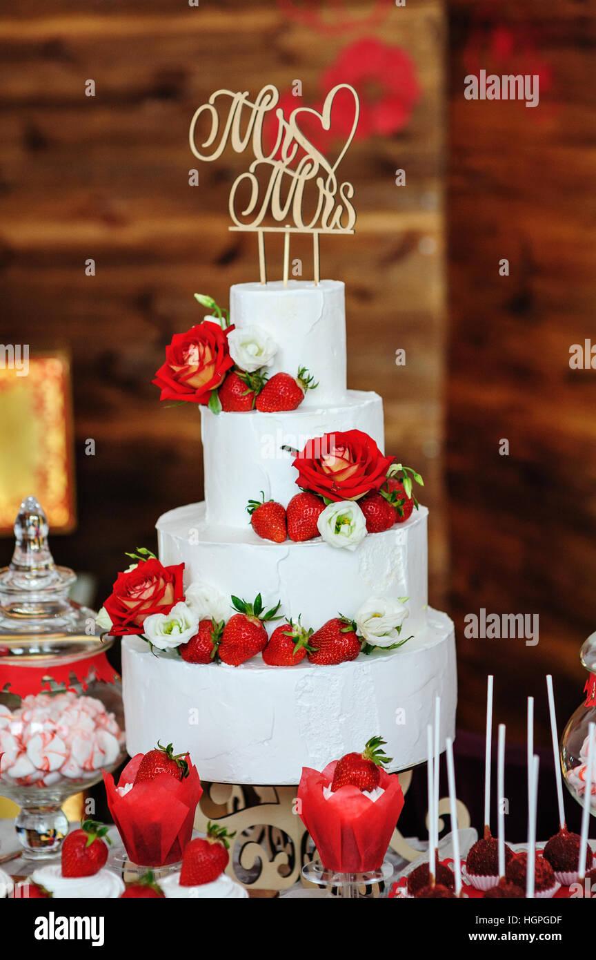 Beautiful Threelayered Wedding Cake Decorated With Red Flowers - Layered Wedding Cake