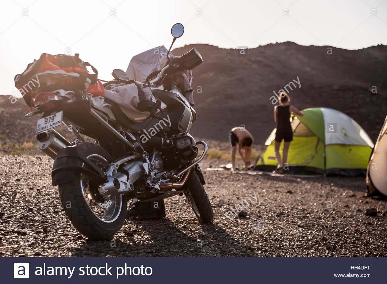 A c&site in a mountain Wadi in the Sultanate of Oman with a enduro motorbike parked and two young person installing their tent & A campsite in a mountain Wadi in the Sultanate of Oman with a ...