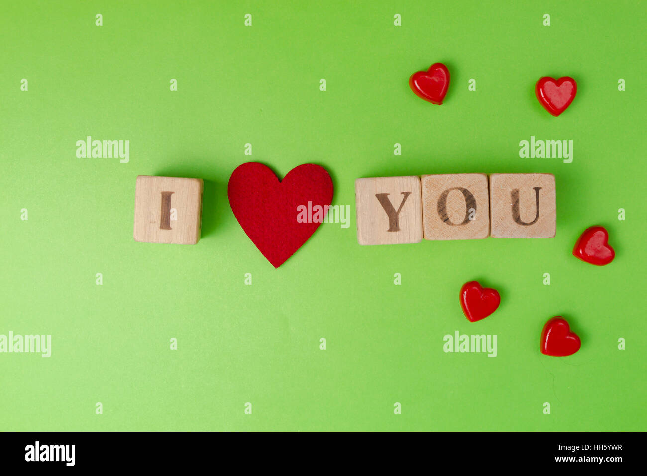 Valentine Hearts And Rustic Alphabet Blocks That Spell Out I Love You On  Greenery Background.