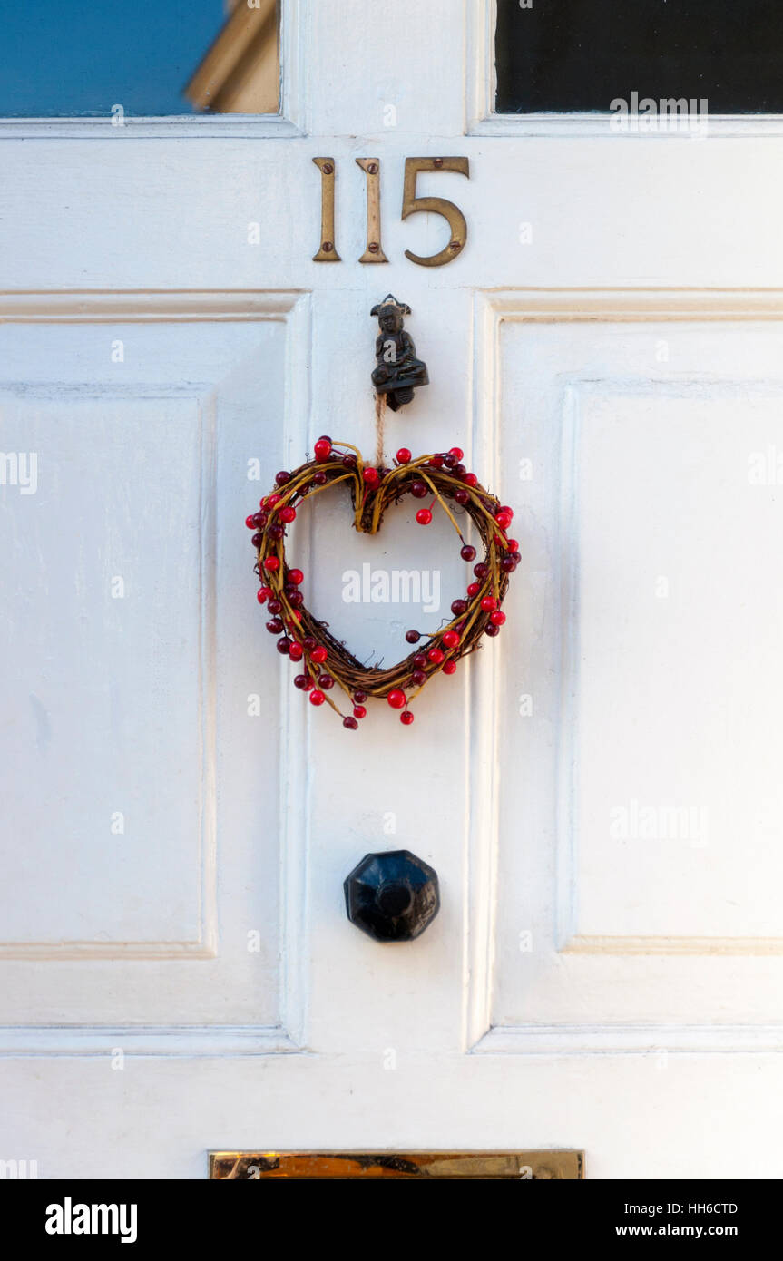 Christmas wreath heart shaped with berries on front door stock christmas wreath heart shaped with berries on front door rubansaba