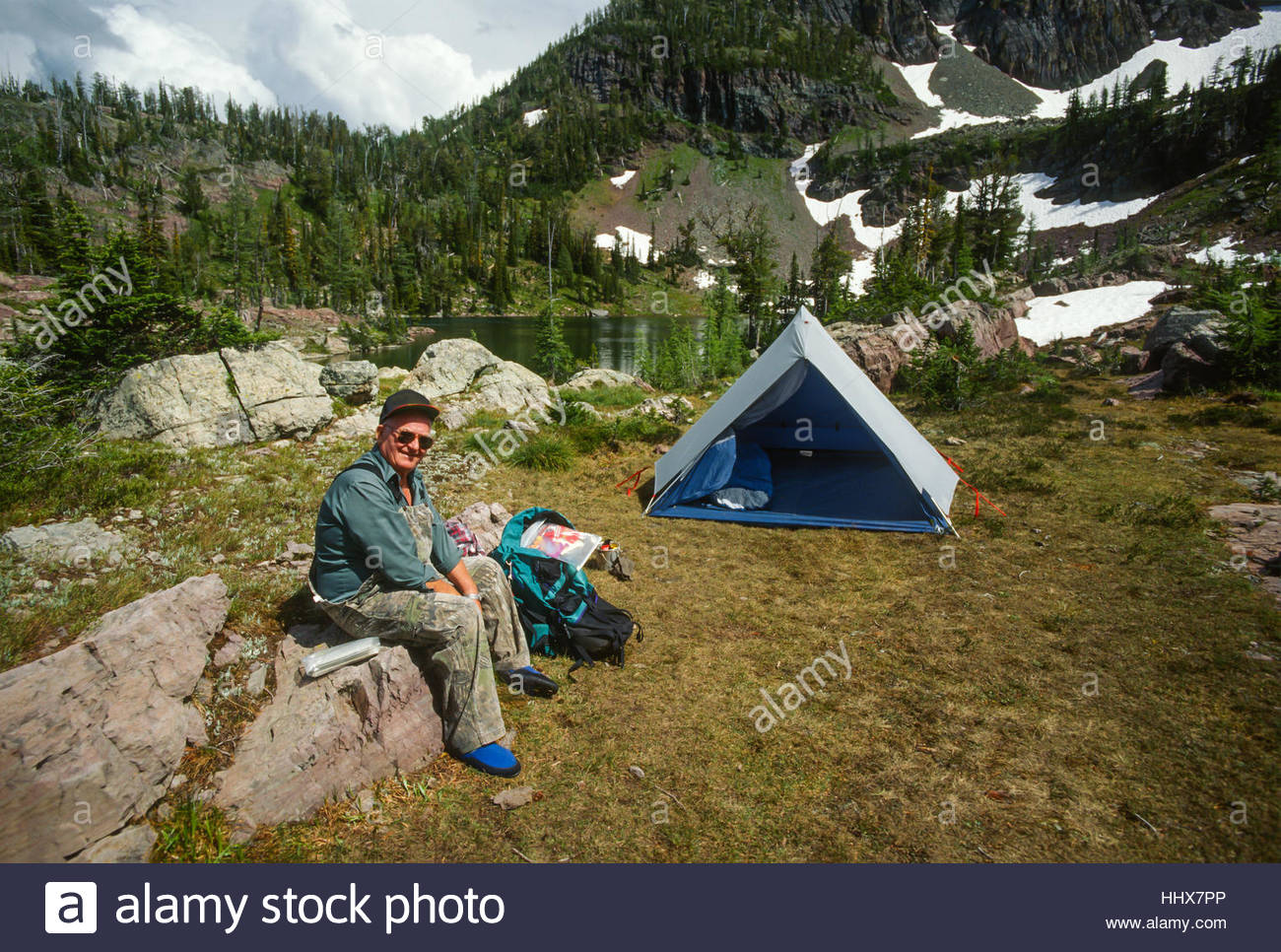 Older Man Resting Sitting on a Rock Next to His Backpacking Tent C&ing at a Small mountain Lake & Older Man Resting Sitting on a Rock Next to His Backpacking Tent ...