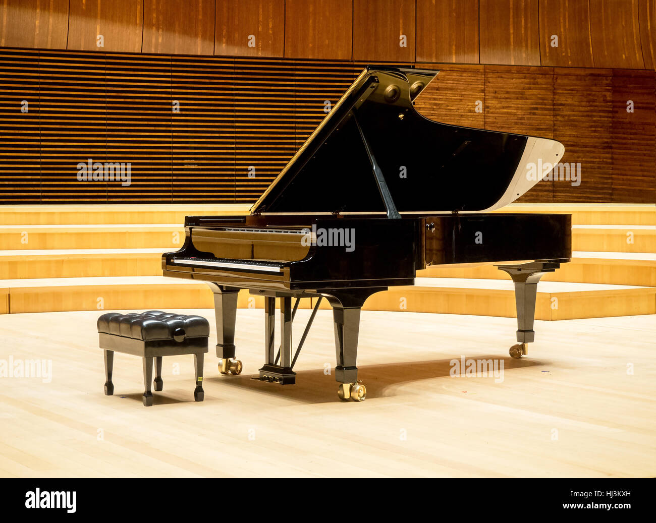 A grand piano on a wooden stage of a concert hall Stock Photo ...