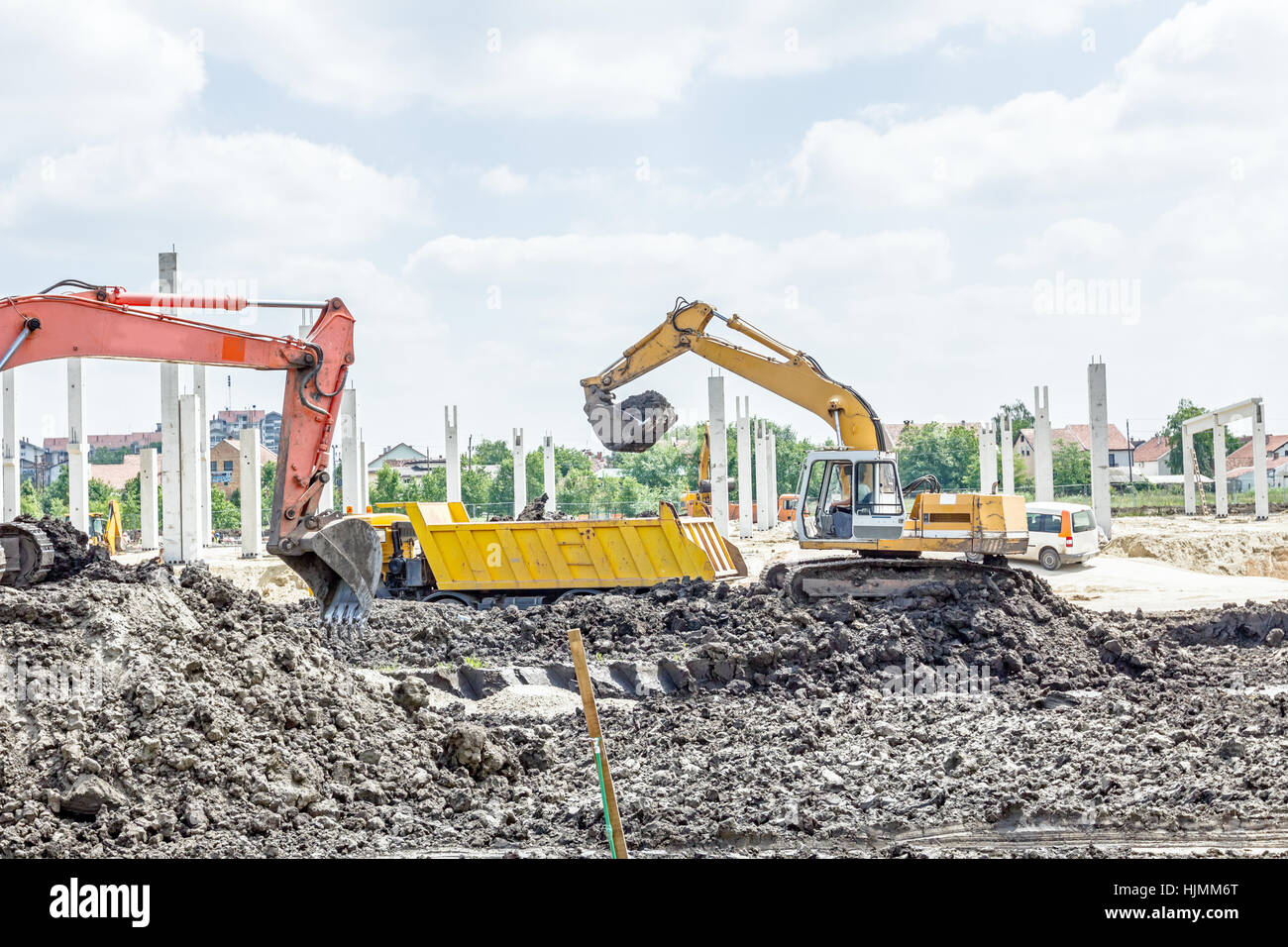 big excavator is filling a dump truck with soil at construction
