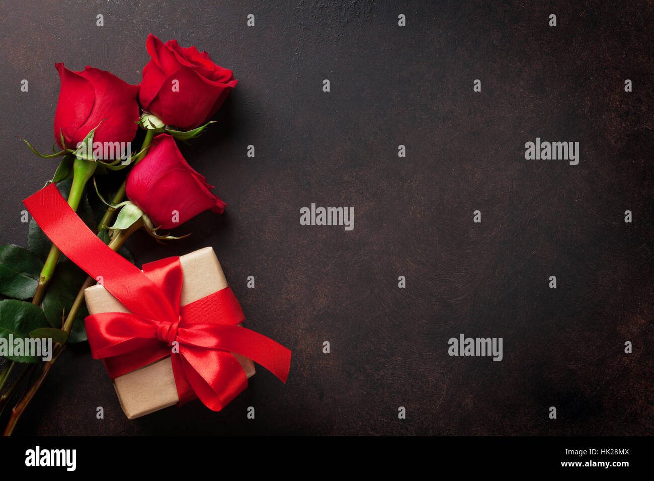 Valentines day greeting card red roses and gift box on stone table valentines day greeting card red roses and gift box on stone table top view with space for your greetings kristyandbryce Choice Image