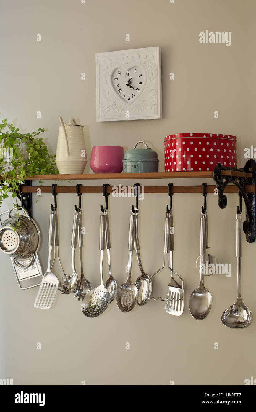 Kitchen Shelf With Hanging Chrome Cooking Utensils With Plant Tins Watering  Can Pots And Clock On Wall