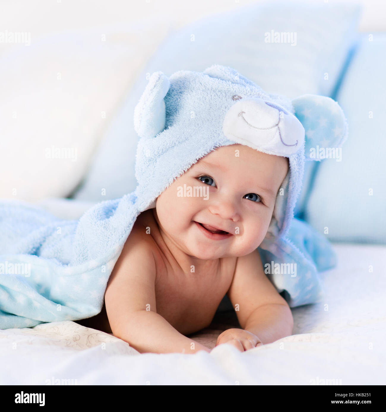 Baby Boy Wearing Diaper And Blue Towel In White Sunny Bedroom Newborn Child Relaxing Bed After Bath Or Shower