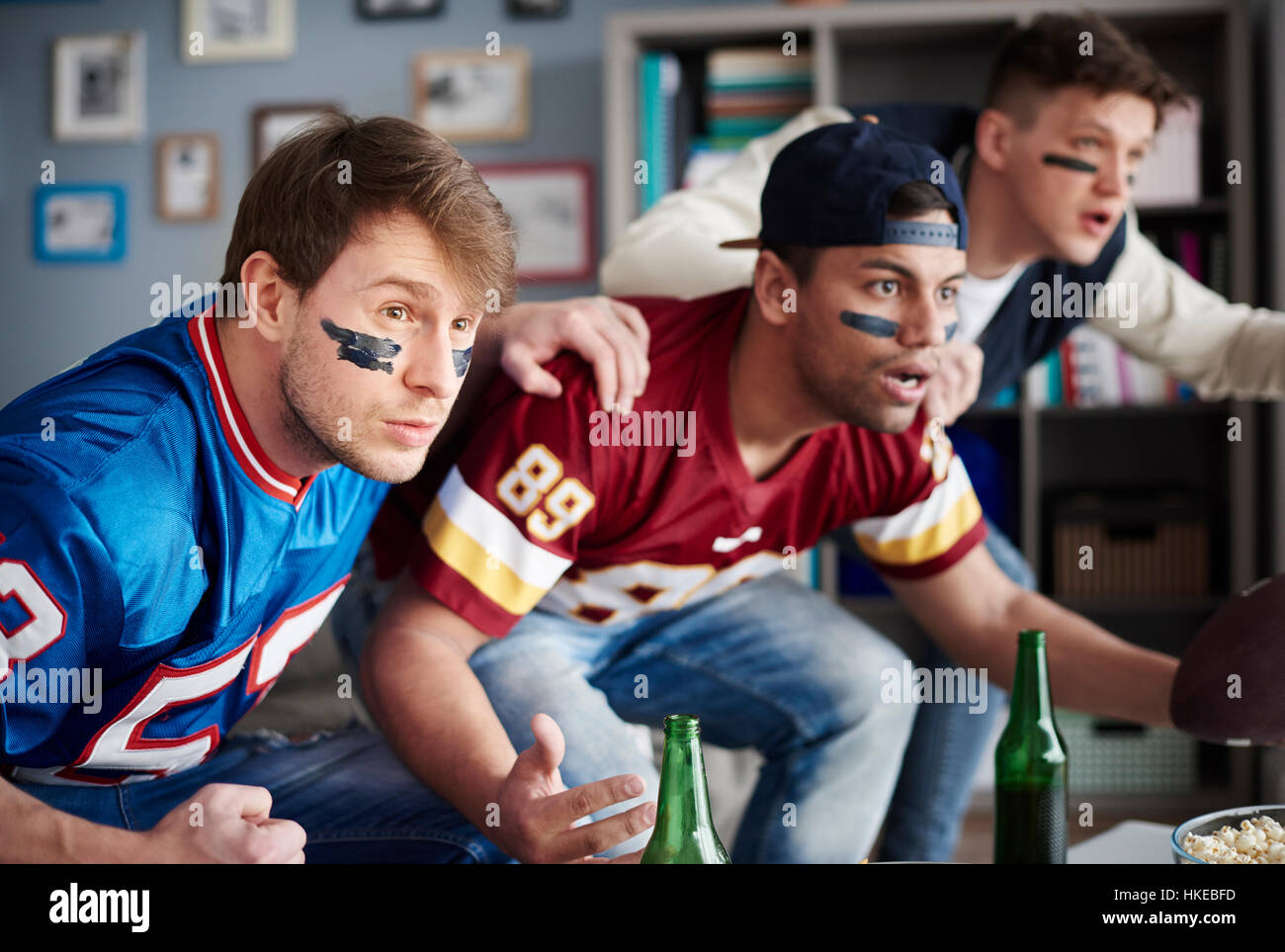front view of excited men watching sports game stock photo front view of excited men watching sports game