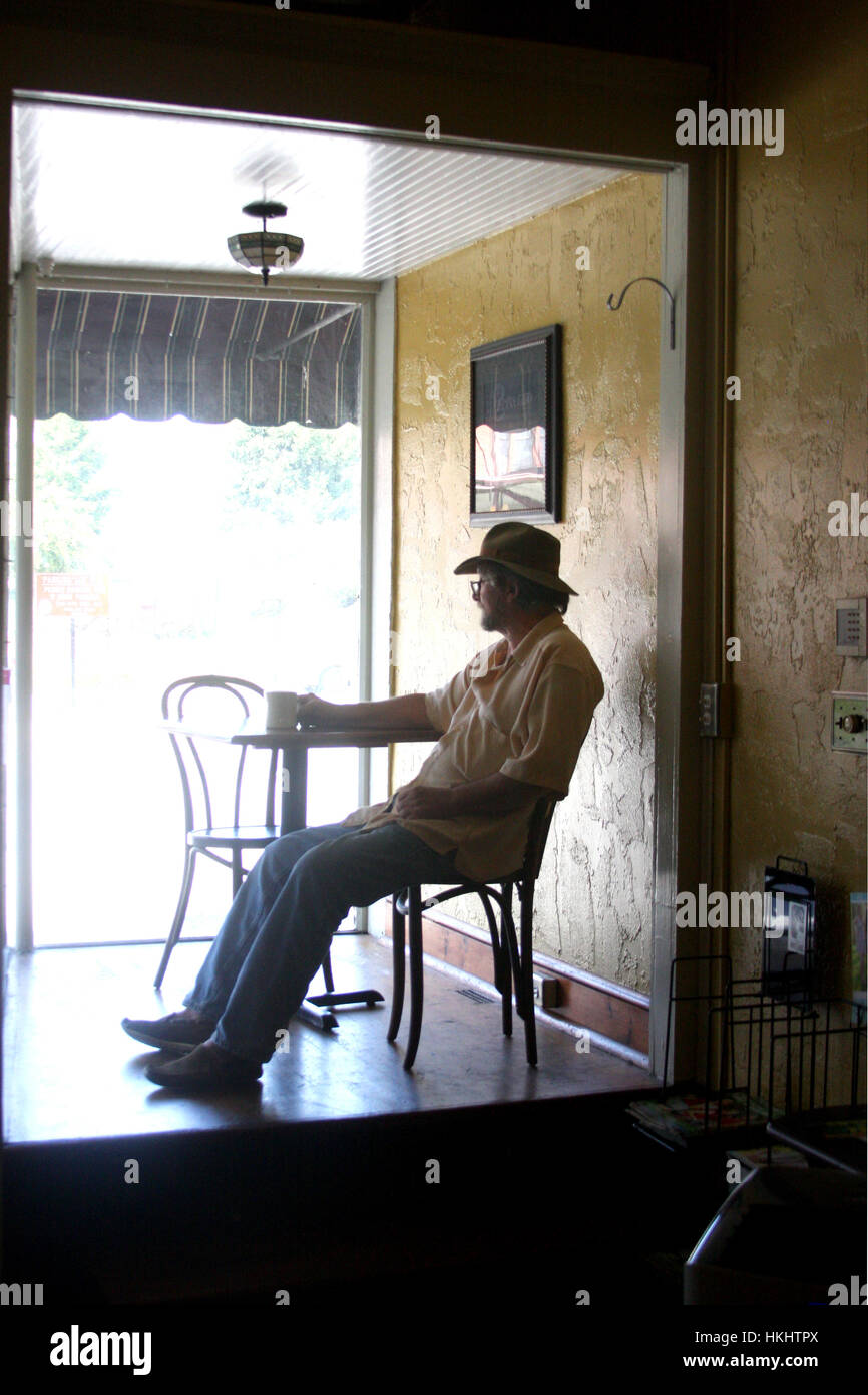 Lonely Boutique In Newmarket Auckland By Rufus Knight: Man Sitting Alone At Table In Coffee Shop Stock Photo