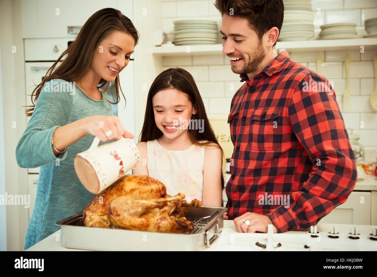 Family preparing Christmas dinner turkey in kitchen Stock Photo ...