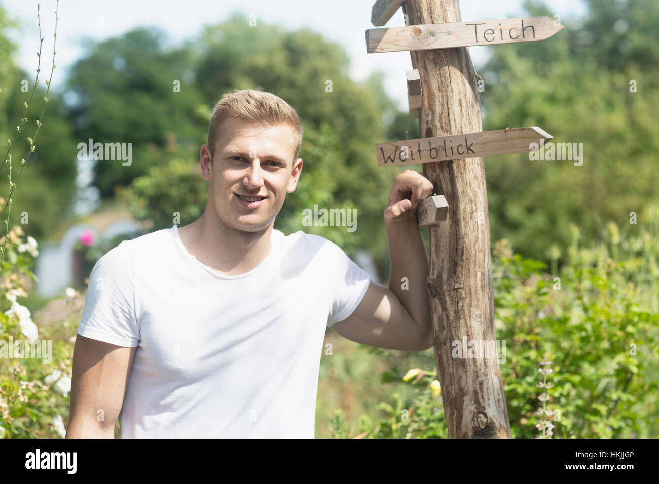 young man standing by wooden post in urban garden freiburg im stock photo royalty free image. Black Bedroom Furniture Sets. Home Design Ideas