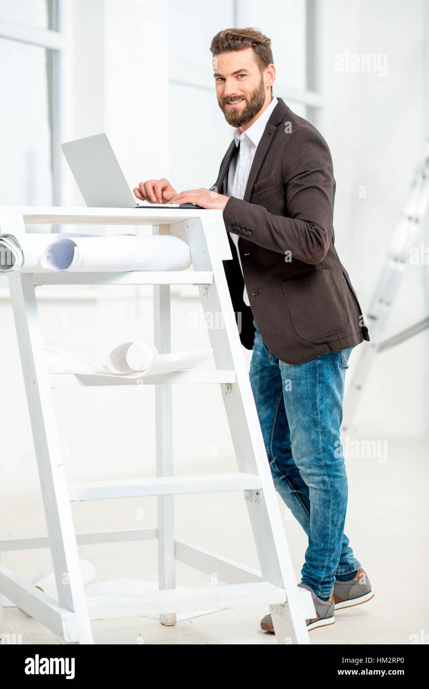 Charming Architect Or Designer Working With Laptop On The Ladder With Paper Drawings  In The Bright Room For Renovating