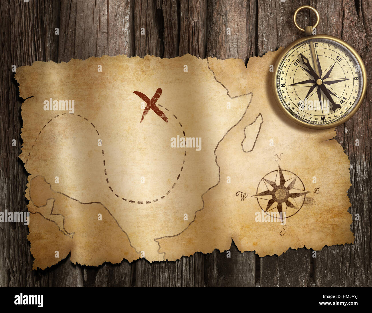 old nautical compass on wood table with treasure map stock