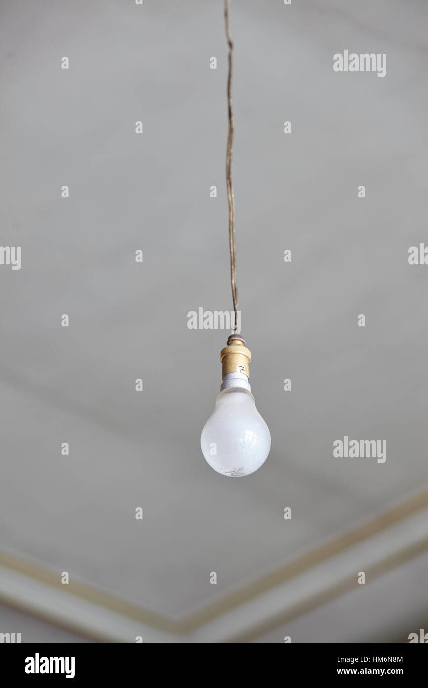 Old light bulb hanging on a power line from the ceiling of an old old light bulb hanging on a power line from the ceiling of an old building stuccoed ceiling in a mansion aloadofball Choice Image