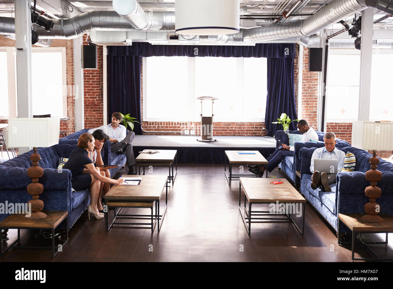 office relaxation. Businesspeople Working In Relaxation Area Of Modern Office