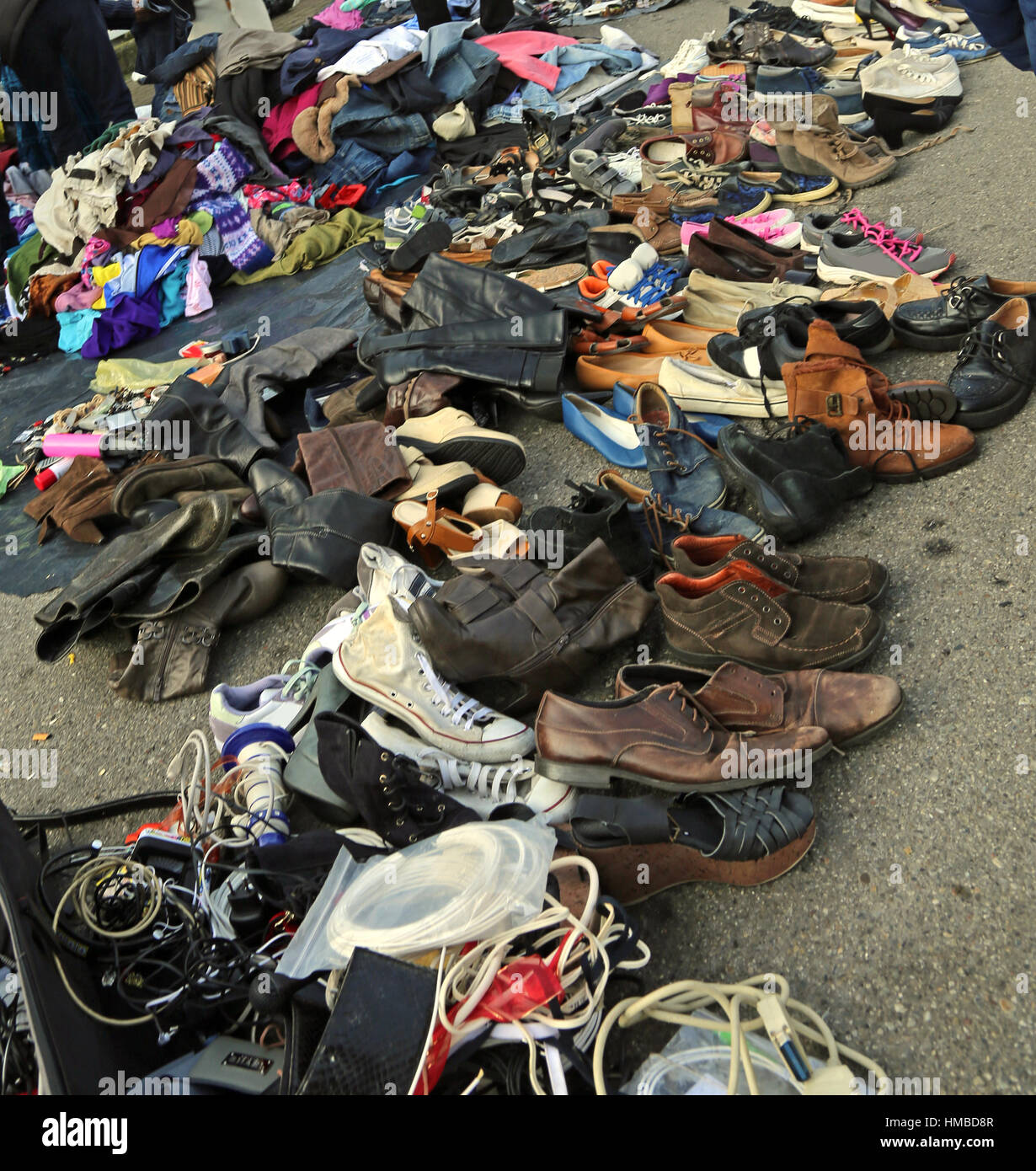 used clothes for sale at outdoor flea market with shoes and old ...