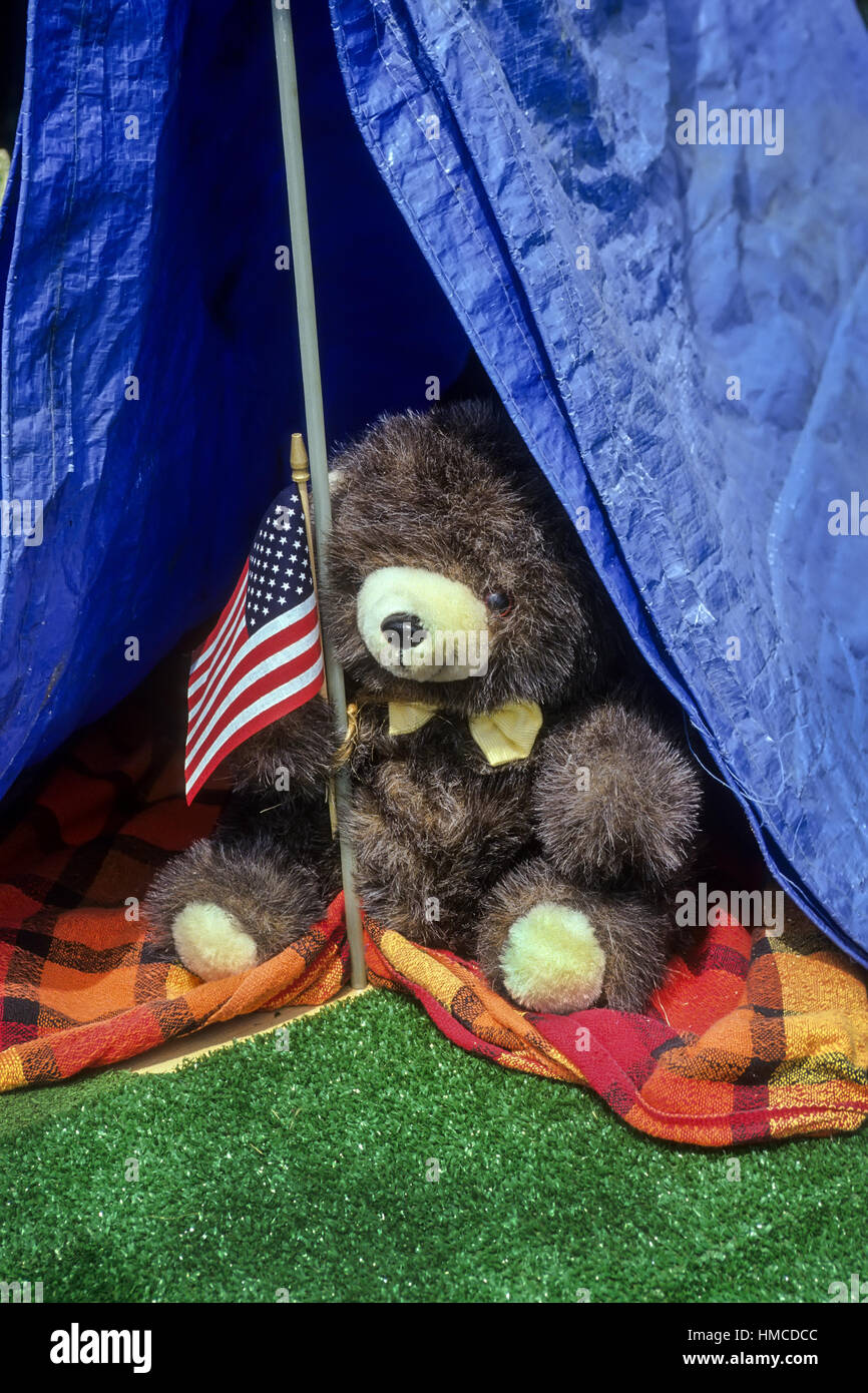 A stuffed bear toy holds an American flag inside a blue tent on Independence Day in the USA & A stuffed bear toy holds an American flag inside a blue tent on ...