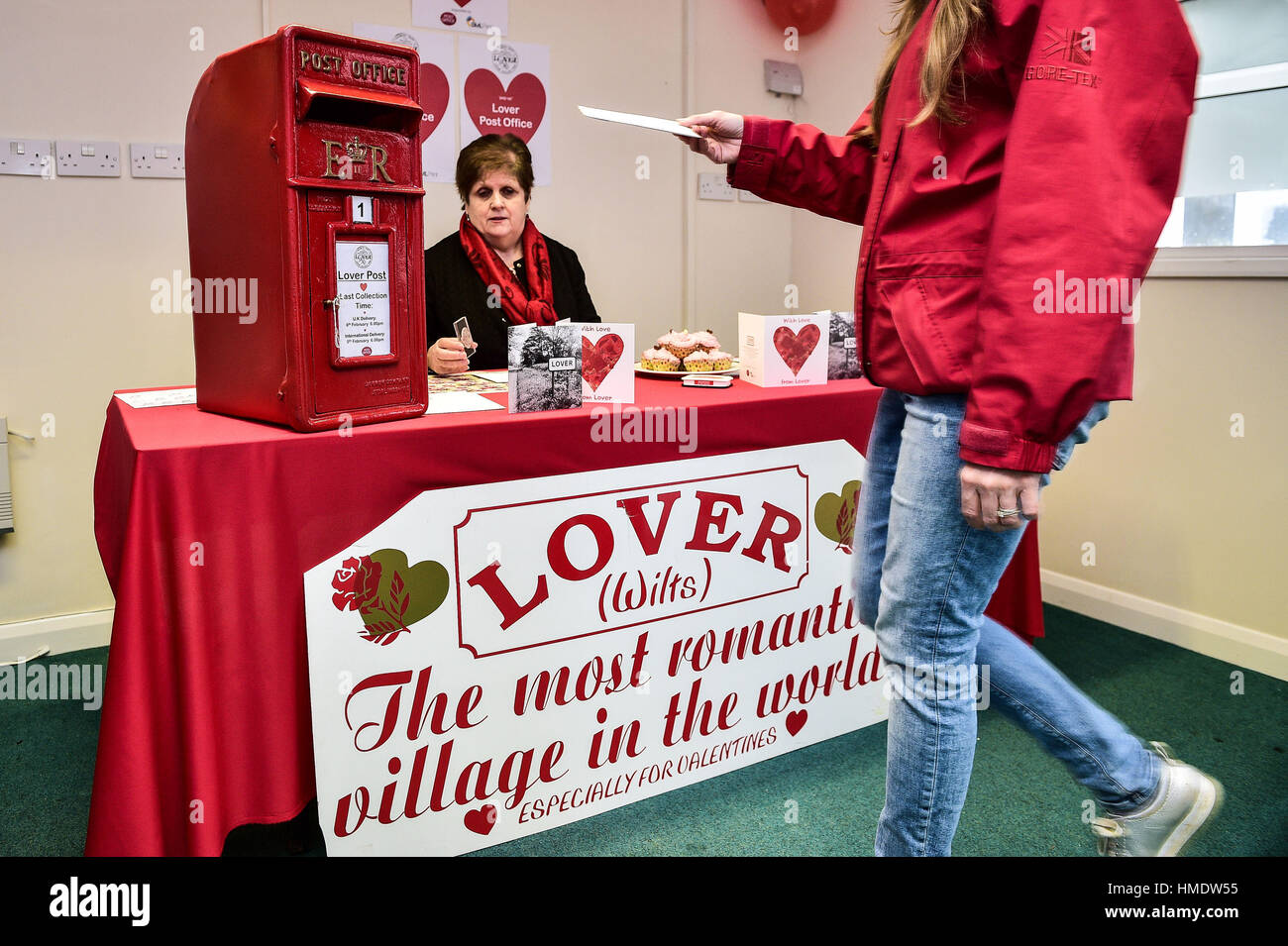 a woman posts a valentines day card in the pop up post office in the