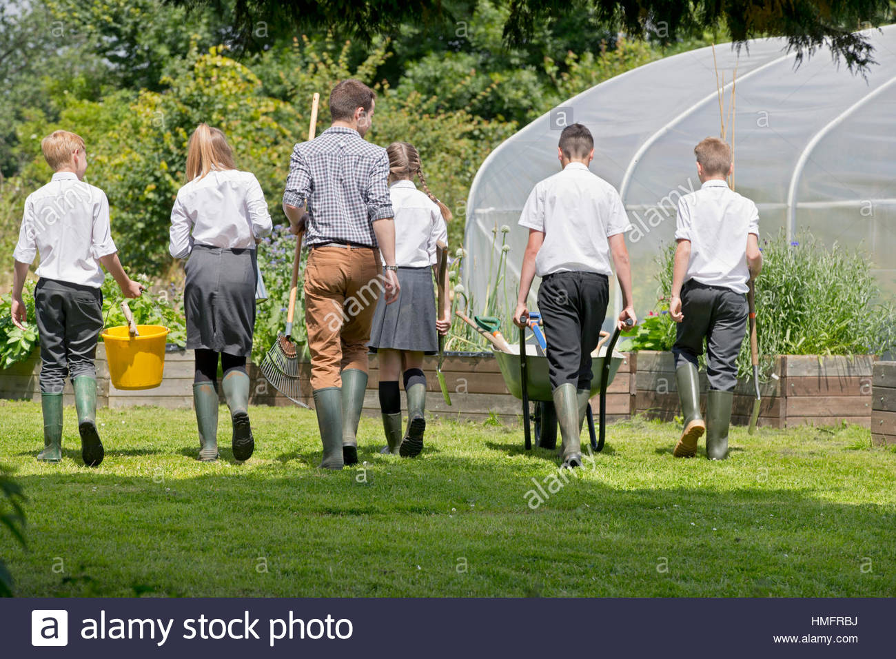 School vegetable gardens -  Teacher And Middle School Students With Wheelbarrow Learning Gardening In Vegetable Garden Stock Photo