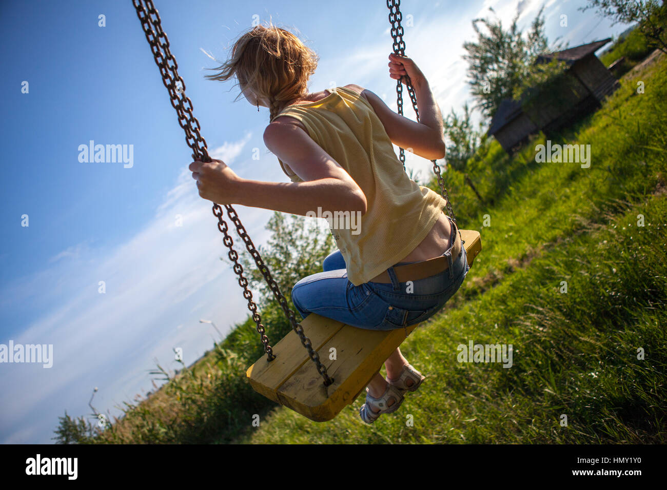 Girl swinging on a swing in the village stock photo for Swingvillage