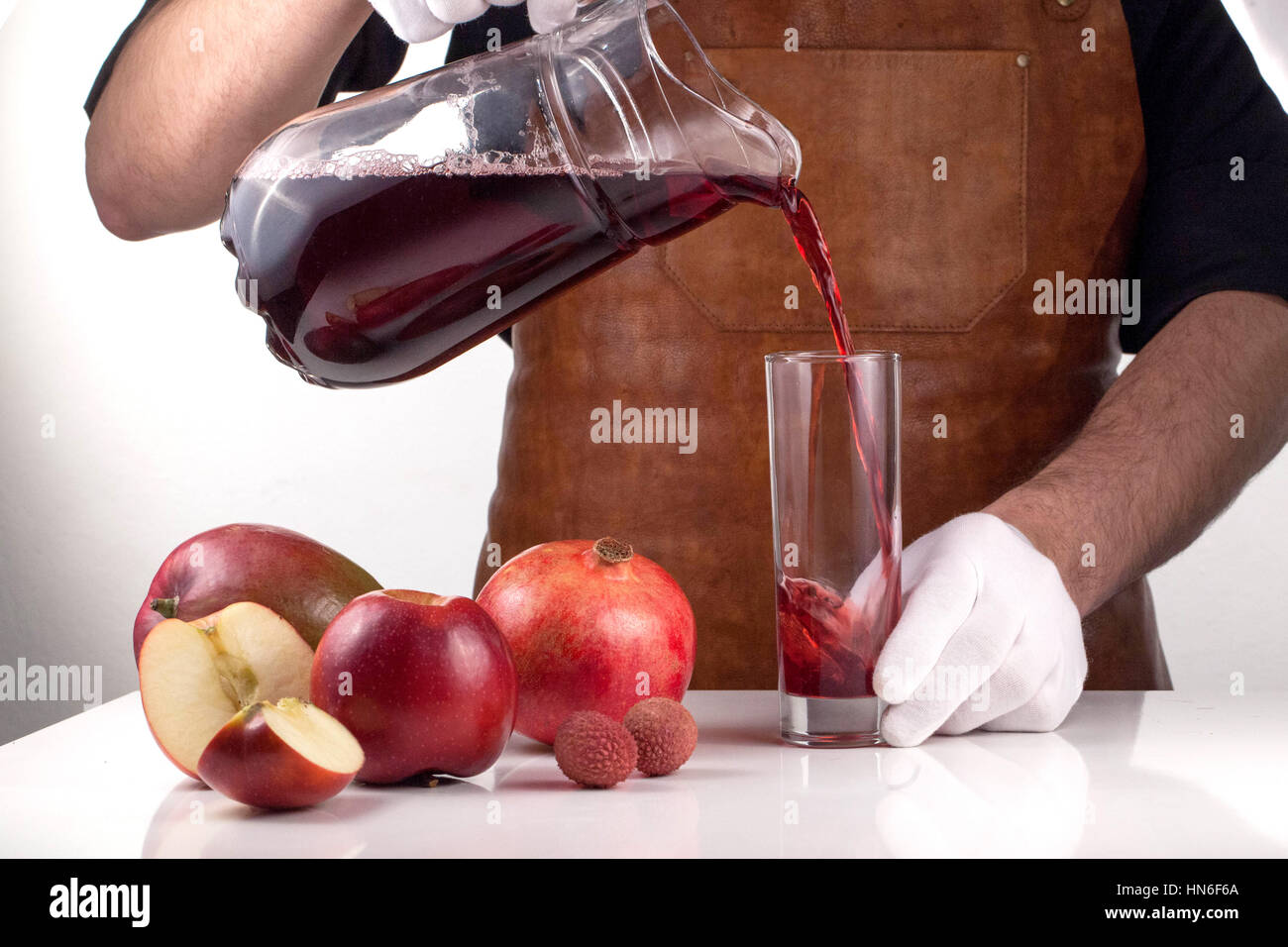 man pouring juice into a glass composition of red fruits on a