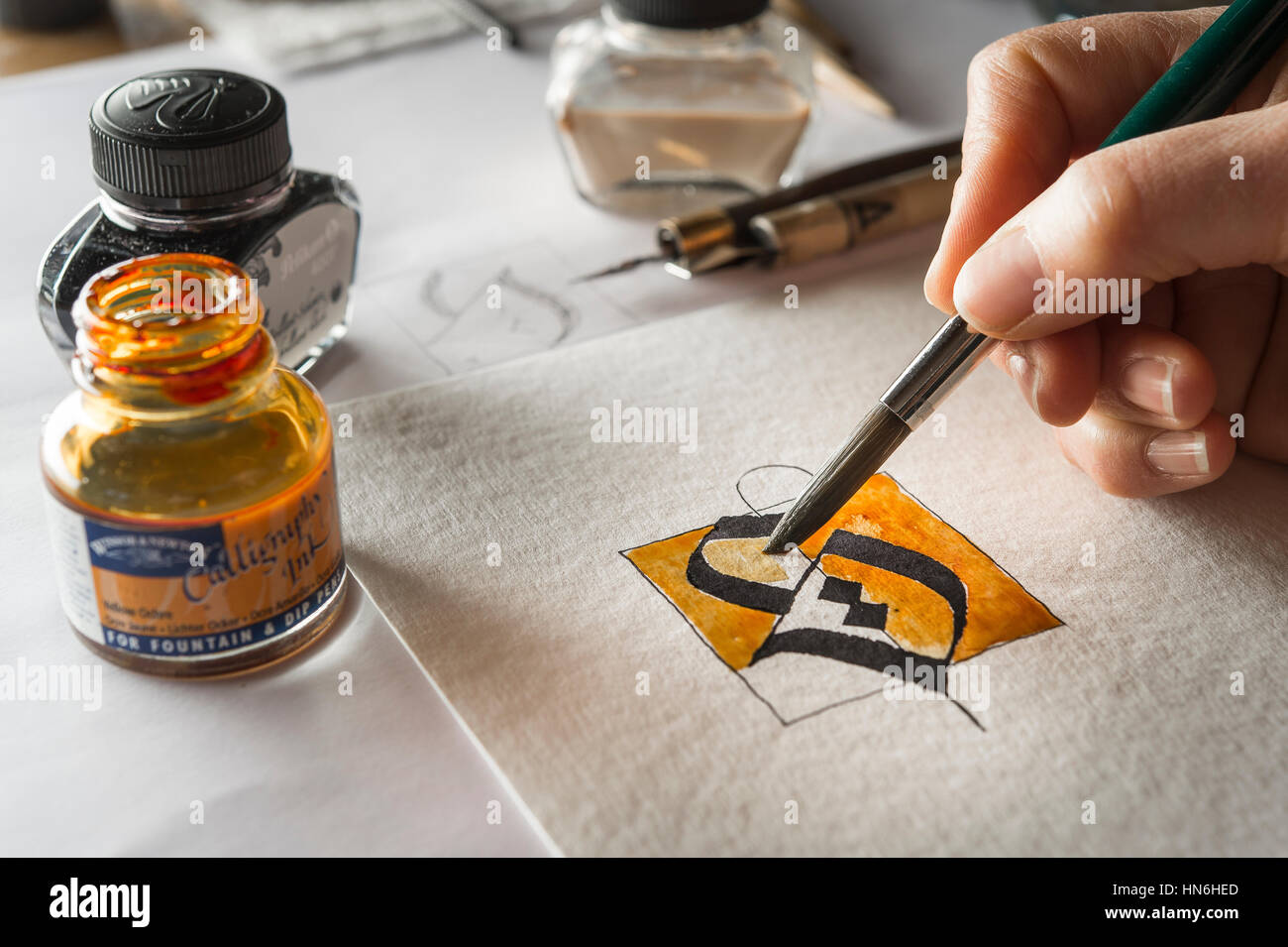 Calligraphy studio hand paints surface with brush letter s on