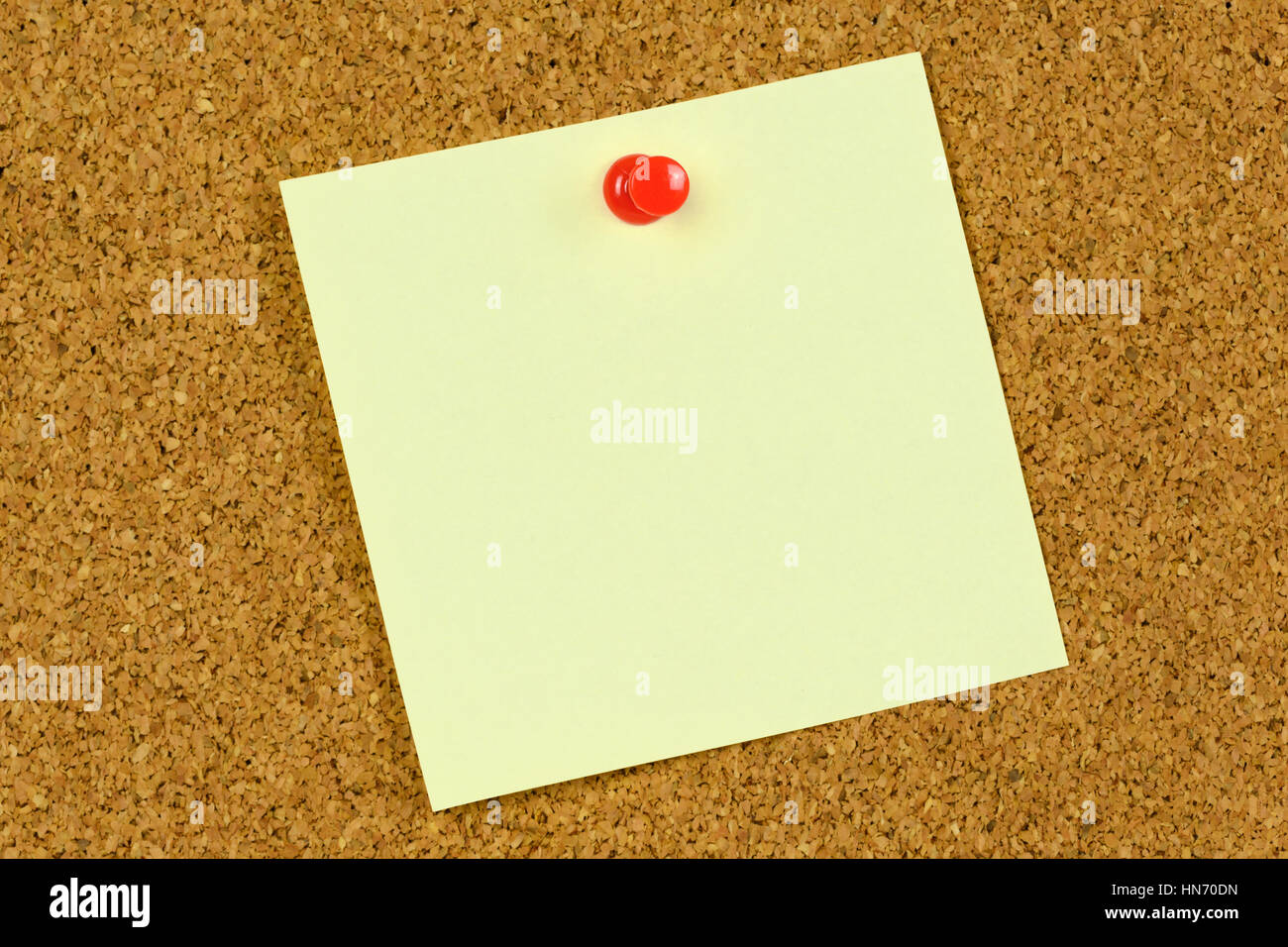 blank yellow sticky note held on a cork notice board with a red pushpin