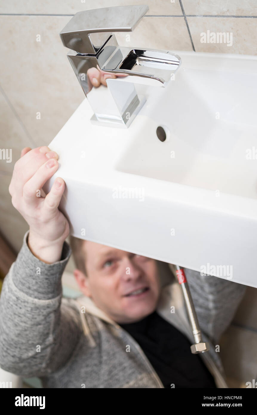 Young man attempting do it yourself diy plumbing at home under a young man attempting do it yourself diy plumbing at home under a sink fitting a new tap with funny expression on his face solutioingenieria Choice Image