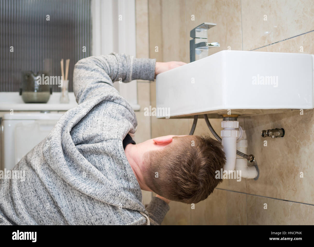 Rear view of a young man attempting do it yourself diy plumbing at rear view of a young man attempting do it yourself diy plumbing at home under a sink fitting a new tap solutioingenieria Choice Image