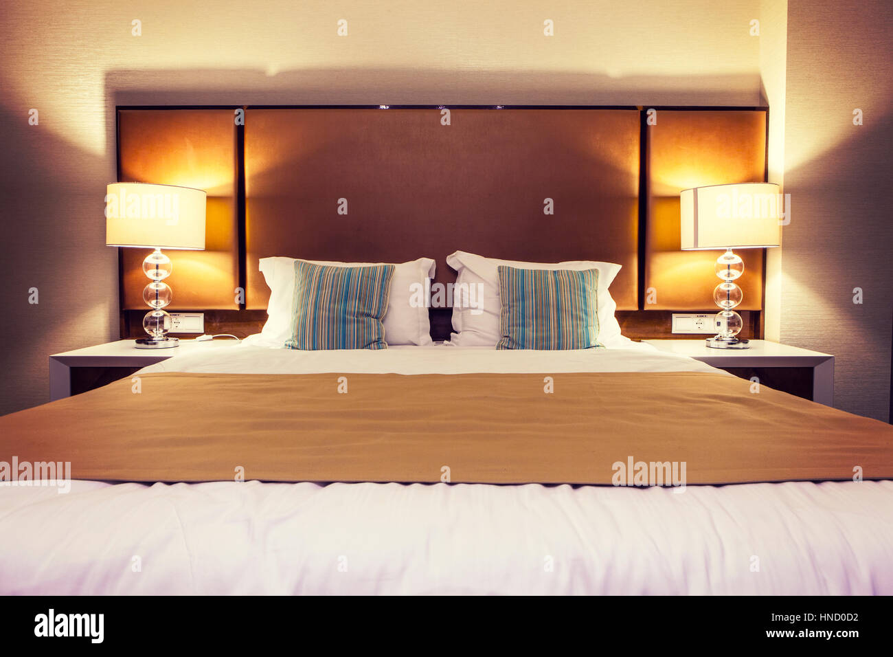 front view of hotel bed with light on on the side and colorful