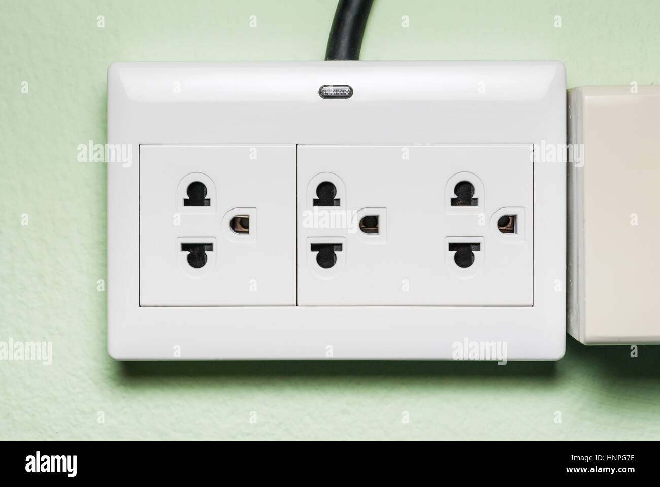 White AC Electric Outlet with Indicator Lamp on Green Wall Stock ...
