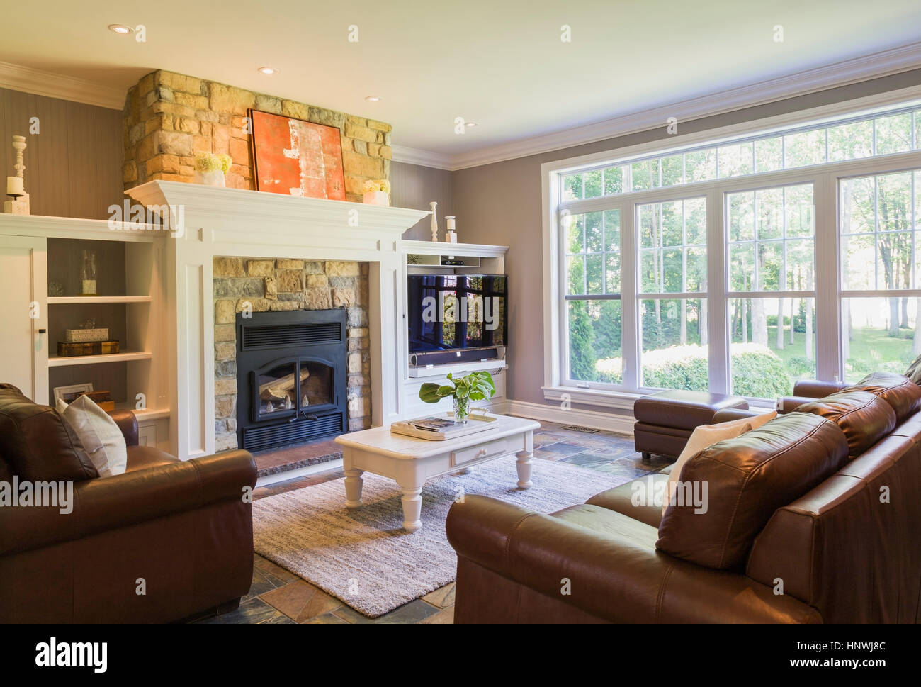 Brown leather sofa, sitting chairs and natural stone fireplace in ...