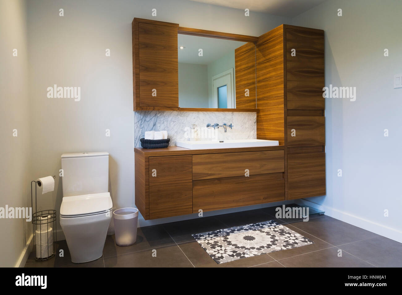 White high back flush toilet and american walnut wood vanity with white high back flush toilet and american walnut wood vanity with rectangular sink and ceramic tile flooring quebec canada dailygadgetfo Choice Image