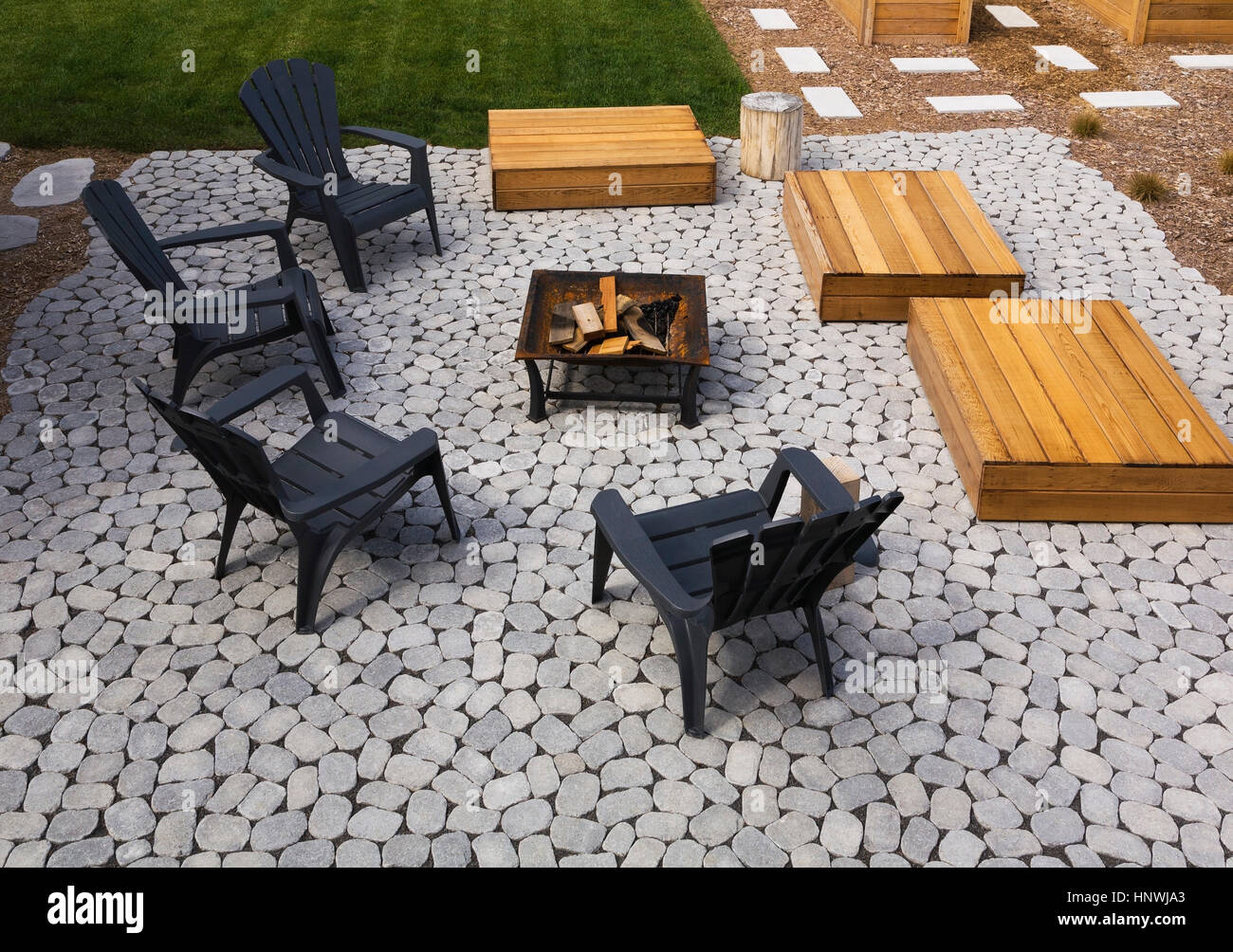 Paving Stone Patio With Adirondack Chairs, Red Cedar Wooden Bench Platforms  Around A Metal Firepit In Backyard, Quebec, Canada