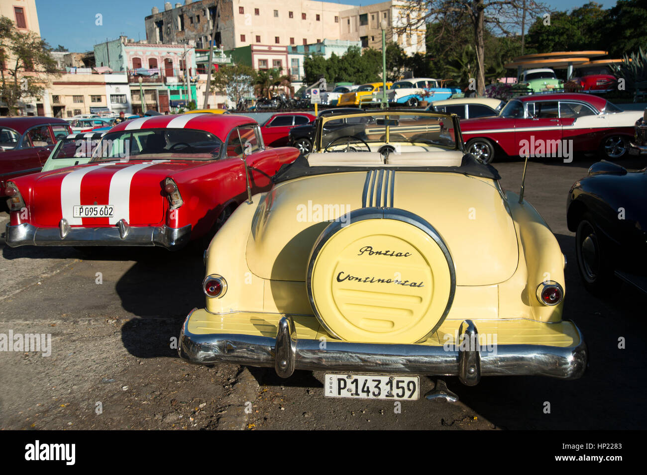 Brightly painted fully restored 1950\'s American cars parked together ...