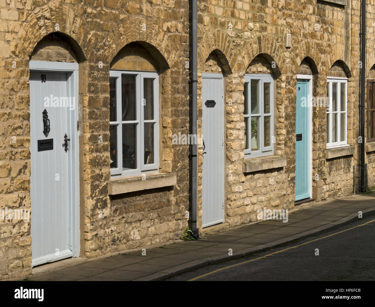 Row of old stone terraced cottages with arch window and front door ...