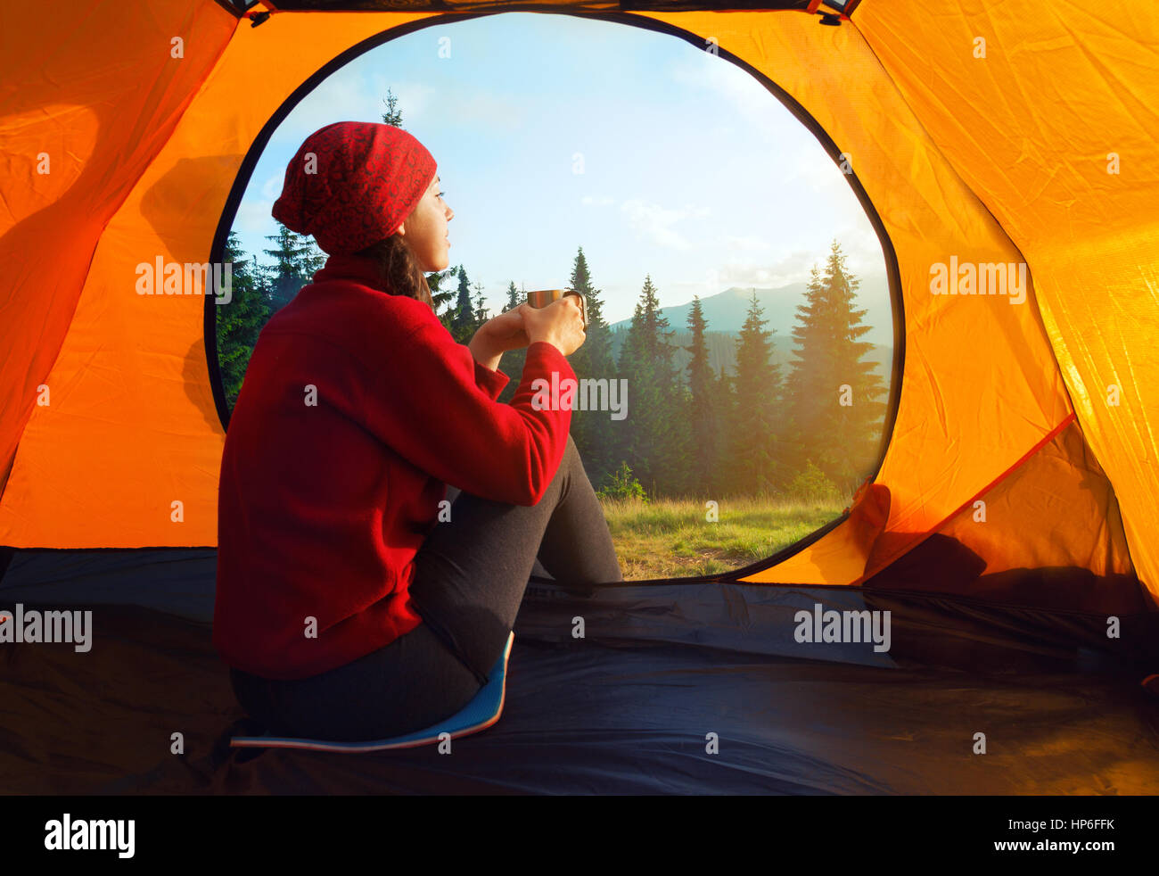 View from inside a tent on mountains landscape. C&ing concept. Sunset inside a tent. Young woman sitting in the tent with cup looking at the mountai & View from inside a tent on mountains landscape. Camping concept ...