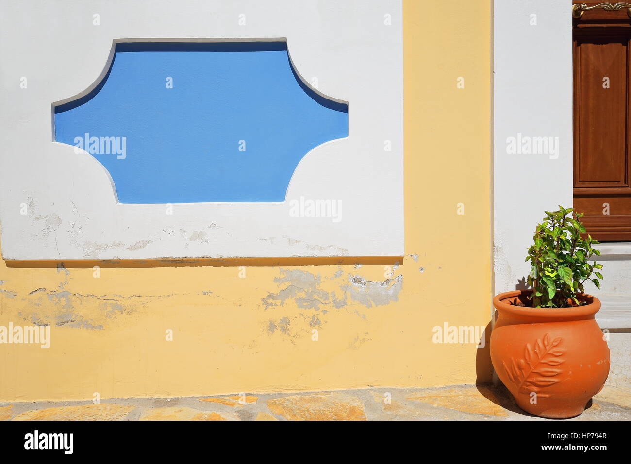Blue decorative form inscribed on white molding upon the yellow wall ...