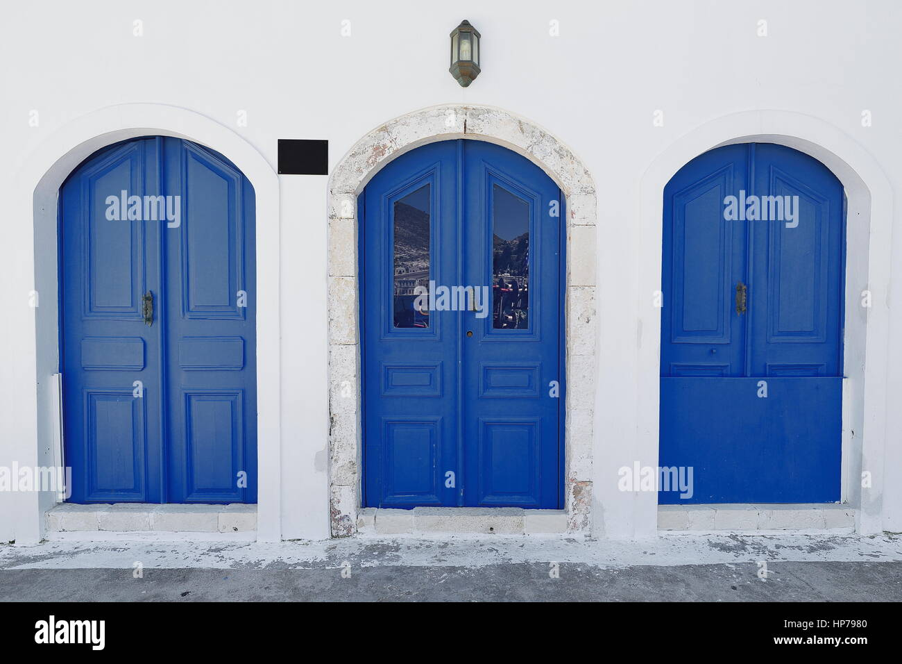 Three blue wooden doors on the whitewashed wall of a restored neoclassical house facing the waterfront of the main harbor in the center of town area : restored doors - pezcame.com