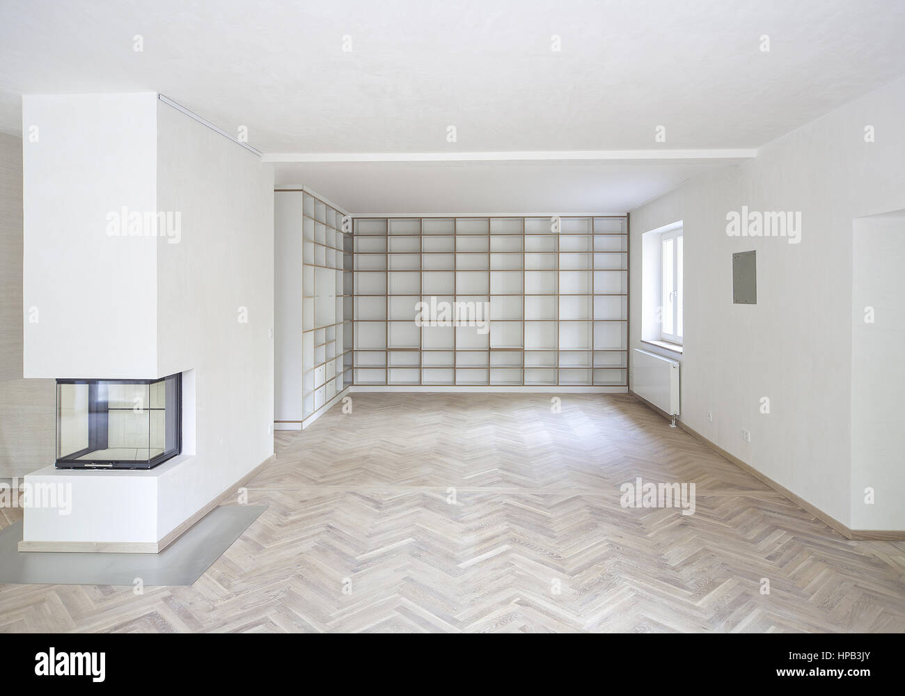 Weißer Parkettboden leerer weisser wohnraum mit parkettboden und regalwand stock photo