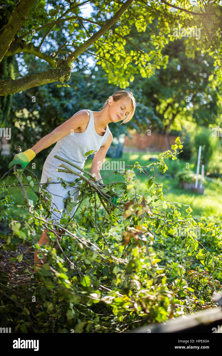 pretty young woman gardening in her garden cutting branches
