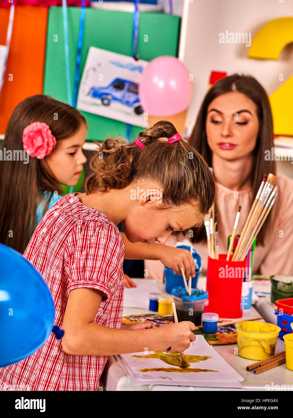 children painting and drawing in kids club craft lesson in primary school kindergarten teacher who smiling help small students group people work to - Children Painting Images