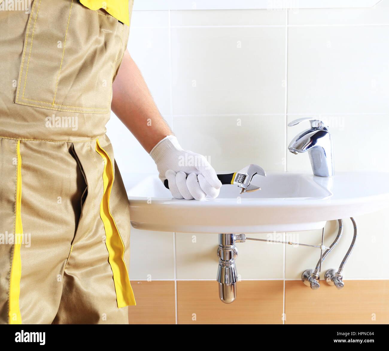 Plumber In Uniform In Bathroom. Plumber Holding Wrench