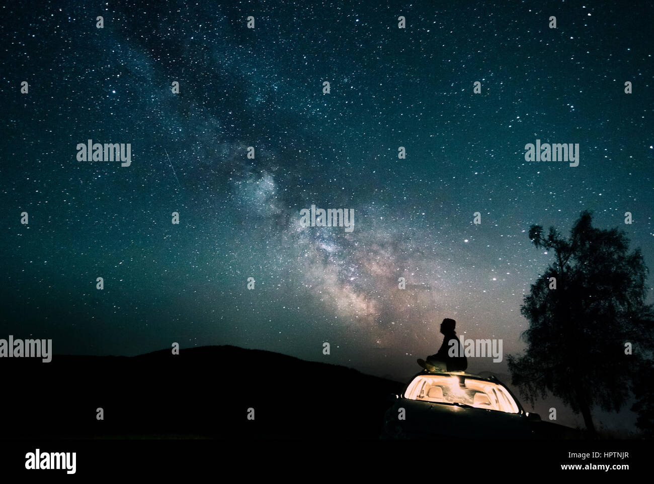 Austria Mondsee Silhouette Of Man Sitting On Car Roof Under Starry Stock Photo Royalty Free