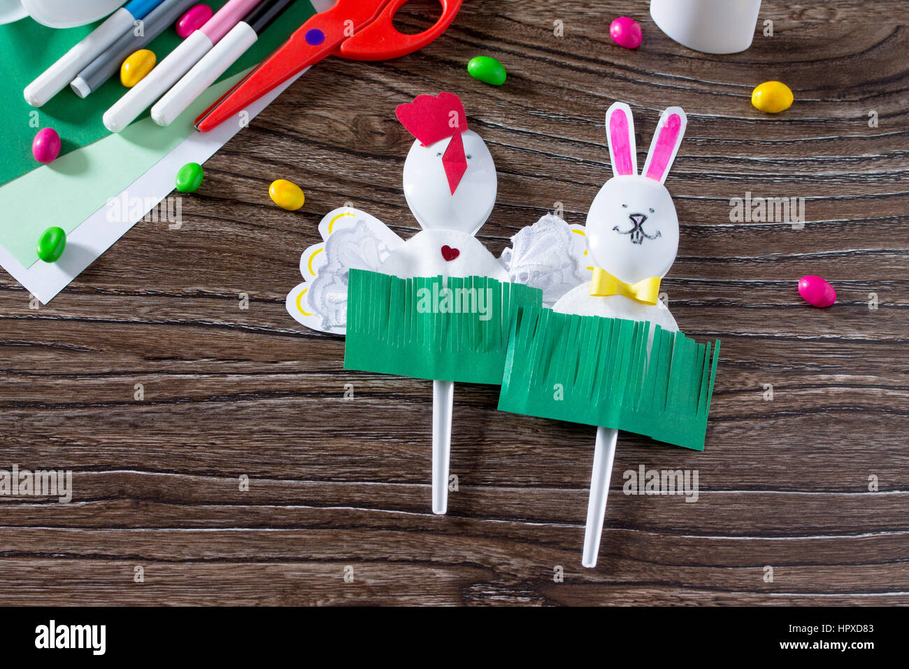 The child creates an easter gift toy easter bunny paper glue and the child creates an easter gift toy easter bunny paper glue and plastic spoons on a wooden table made by hand childrens art project needlework negle Gallery